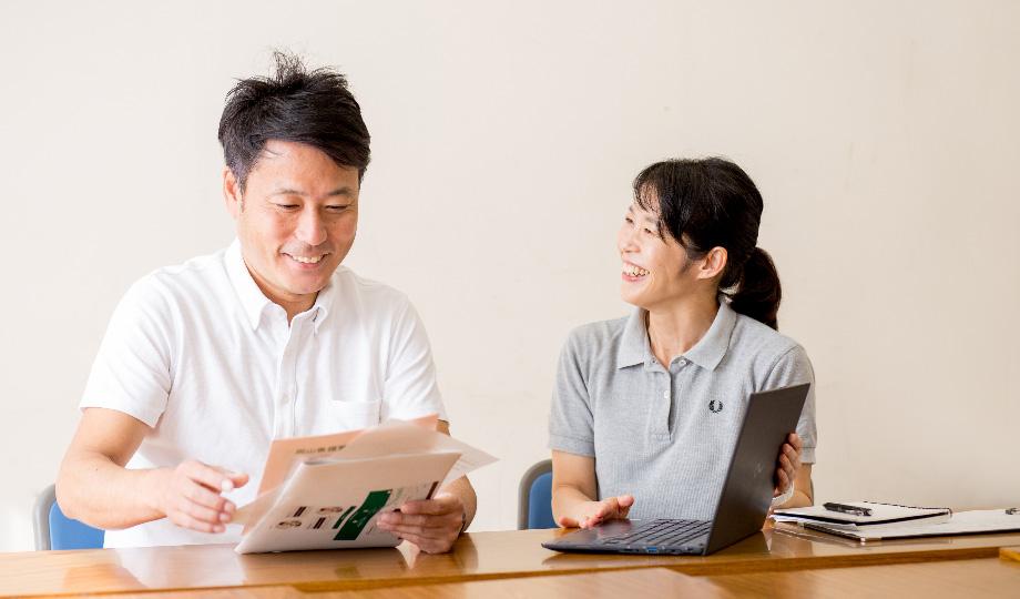 支援員が利用者さんへの支援方法を話し合っている写真。